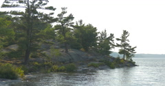 View of rocks and trees on the shore of the lake at Killbear Provincial Park Stock Footage