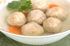 Chicken soup with Kneidlach (Matzah bolls) - stock photo