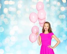 Stock Photo of happy young woman or teen with helium air balloons