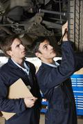 Mechanic And Trainee Working Under Car - stock photo