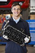 Apprentice Mechanic Holding Engine Block - stock photo