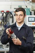 Apprentice Engineer Checking Component In Factory - stock photo