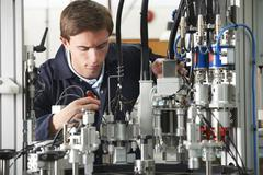 Engineer Working On Complex Equipment In Factory - stock photo