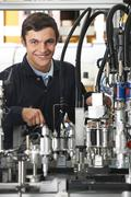 Stock Photo of Trainee Engineer Working On Machinery In Factory