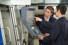 Engineer Instructing Trainee On Use Of Compterized Cutting Tool - stock photo