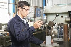 Teenage Apprentice Operating Drill In Factory - stock photo