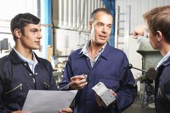 Team Of Engineers Having Discussion In Factory Stock Photos