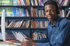 Male Teenage Student Working At Computer Wearing Headphones - stock photo