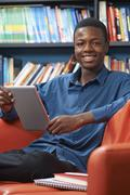 Male Teenage Student Using Digital Tablet In Library - stock photo