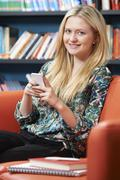 Female Teenage Student Using Mobile Phone In Library - stock photo