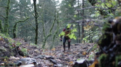 Backpacker carrying mug hikes up a trail to collect water from a stream. Stock Footage