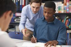 Teacher Helping Male Pupil In Class - stock photo