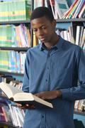 Male Teenage Student Reading Book In Library - stock photo
