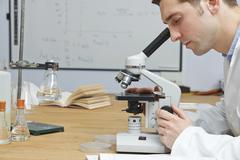 Stock Photo of Male Biology Teacher Looking Through Microscope In Classroom
