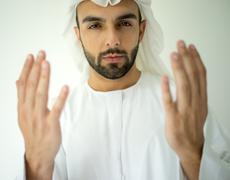 Arab man praying with hands up Stock Photos