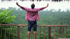 Young man with wide open arms enjoying day on terrace Stock Footage
