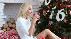 Beautiful girl drinking tea at home. Decorated Christmas tree Stock Footage