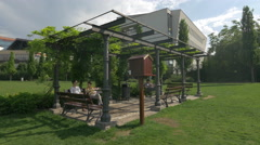 Young people relaxing under a steel pavilion in Iulius Park, Cluj-Napoca Stock Footage