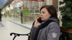 Girl talking on the phone while sitting on the bench at the mall Stock Footage