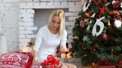 Happy girl opened Christmas gifts near a Christmas tree - stock footage