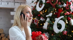 Stock Video Footage of Young woman making a call at Christmas on her mobile phone to wish a family