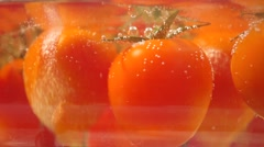 Small ripe tomatoes boiling in a glass pan Stock Footage