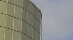 Detail golden steel glass modern office building against flying clouds in sky Stock Footage