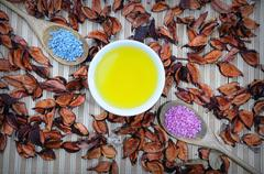 Body oil and blue/pink sea salt on background. Scattered leaves on wooden tab - stock photo