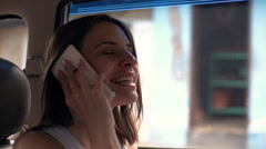 Happy, pretty woman talking on cellphone in car, super slow motion  Stock Footage