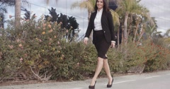 Smiling confident woman striding along a sidewalk - stock footage