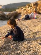 Stock Photo of Small girl playing on the beach with mother in background