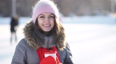 Girl with mug of hot drink on ice skating rink Stock Footage