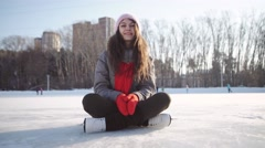 Young woman fell down on skating rink and holding to her knee Stock Footage