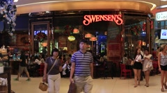 People walking near Swensen's Restaurant in Siam Paragon Mall. Bangkok, Thailand Stock Footage