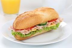 Sub deli sandwich baguette for breakfast with ham and orange juice Stock Photos