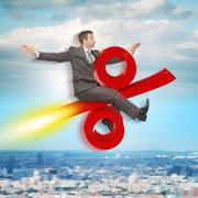 Businessman flying on percent sign Stock Photos