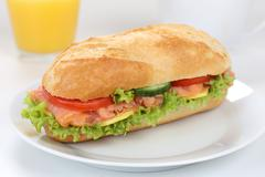 Sub deli sandwich baguette for breakfast with salmon fish and orange juice Stock Photos