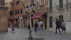 Men and women walking on a street with boutiques in Venice - stock footage