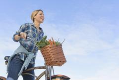 Stock Photo of Portrait of young woman with bicycle