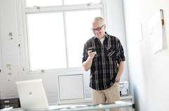 Stock Photo of Man in office using smartphone