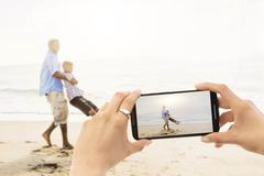 Young woman photographing father with son (12-13) on beach - stock photo