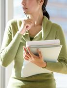 Stock Photo of Mid section of business woman holding documents