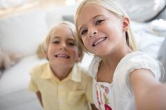 Girl (6-7) and boy (4-5) looking at camera - stock photo