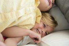 Boy (4-5) and girl (6-7) playing on sofa Stock Photos