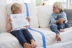 Boy (4-5) sitting on sofa with girl (6-7) holding paper - stock photo