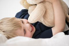 Stock Photo of Smiling boy (2-3) with toy lying down on bed