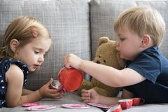 Brother (2-3) and sister (2-3) having tea party with teddy bear Stock Photos