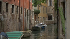 Boats floating along a brick building in a canal in Venice Stock Footage
