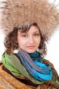 Girl in a fur hat and blue scarf  isolated on white background Stock Photos