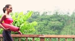 Young, sporty woman unfold mat on terrace Stock Footage